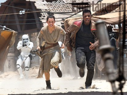 Daisy Ridley's Rey and John Boyega's runaway stormtrooper Finn flee from The First Order on the desert world Jakku in this new shot from Star Wars: The Force Awakens, out Dec. 18.
