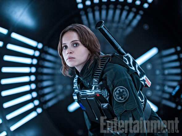 """Jyn Undercover… Rogue One is an ensemble story, but its central figure is Jyn Erso (Felicity Jones), a young woman recruited by the Rebellion to infiltrate the Empire and secure details of its latest weapon – a moon-sized battle station we know as the Death Star. Here we see her in disguise, armed for conflict inside an Imperial corridor. Lucasfilm president Kathleen Kennedy says Jyn starts as an outlaw and """"becomes a kind of Joan of Arc in the story."""""""